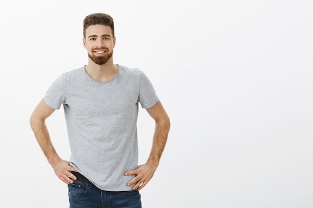 カリスマ的で親しみやすく、熱狂的な魅力的な男性が、腕を腰に当てて自信を持ってポーズをとって手を伸ばすのを提案します。
