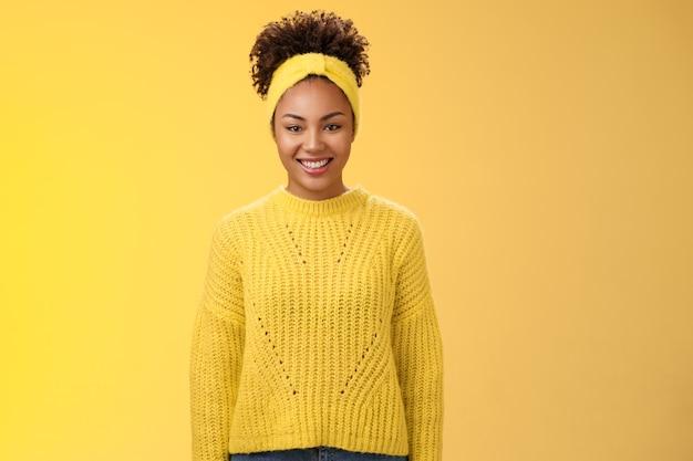 Carismatico amichevole sorridente ragazza nera fascia ricci acconciatura afro ghignando con gioia eccitato partecipare all'evento universitario aiutando in piedi in uscita energizzato sfondo giallo.