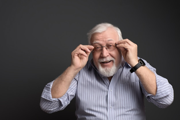 Charismatic, gray-haired man holds his glasses and smiles