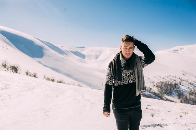 눈 덮인 산의 배경으로 포즈 카리스마 잘 생긴 젊은 남자
