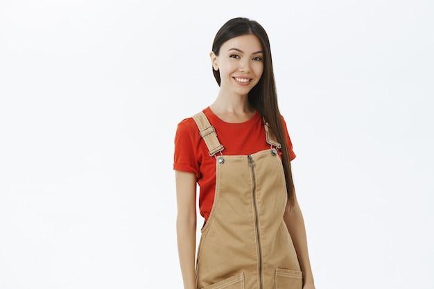 Харизматичная счастливая и расслабленная современная азиатская женщина в коричневом комбинезоне с темными длинными волосами, дружелюбно улыбается