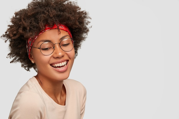 Charismatic happy black curly young lady looks down with broad smile, wears transparent glasses, red headband, laughs at something funny, poses against white wall, blank copy space on right side.