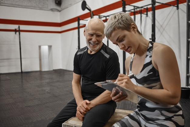 Charismatic happy elderly male with muscular athletic body sitting at fitness center with young blonde female trainer who is writing down results after personal workout with her senior client