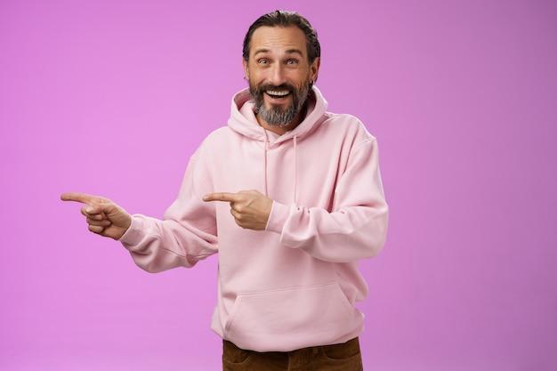 カリスマ的な幸せな格好良い成熟した50代の男性は、スタイリッシュなヒップスターのパーカーを着て、興奮した左手の人差し指を指して、紫色の背景に立って素晴らしい興味深い提案を印象づけました。