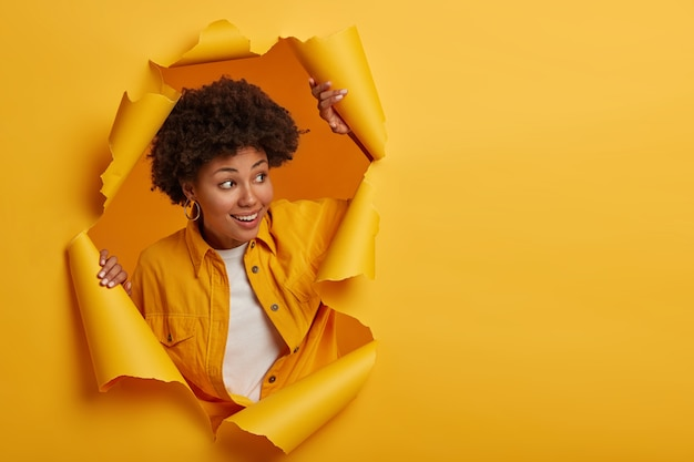 Charismatic joyful afro woman with curly hairstyle turns away, looks on right side, wears fashionable shirt, stands in torn paper hole