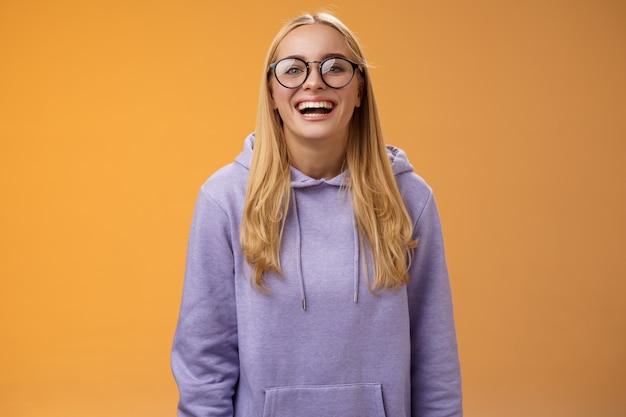 カリスマ的なうれしそうな魅力的な笑顔の女子大学生は、オレンジ色の背景に立っているクラスメートを招待して喜んで笑って笑っている紫色の居心地の良いパーカーを眼鏡でまっすぐに学生。