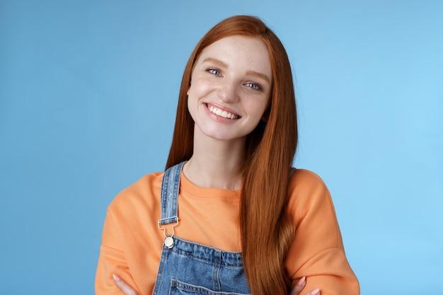 カリスマ的な親切な気持ちの良い赤毛の女の子青い目笑顔フレンドリーに丁寧に聞く顧客立っている青い背景傾斜頭面白がってニヤリとクロスハンズ胸プロ自信ポーズ