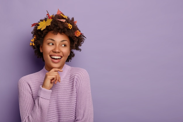 Charismatic lovely woman touches jawline, looks away with happy expression, has autumn leaves on hair, expresses positive emotions, dressed casually