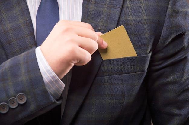 スーツを着たカリスマ的な男がカードを胸ポケットに入れる