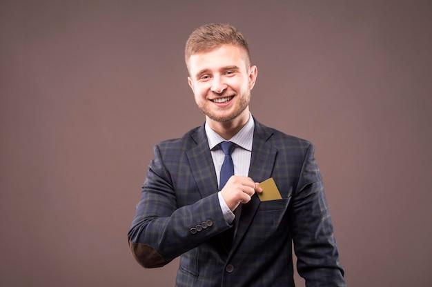 スーツを着たカリスマ的な男が微笑んでカードを胸ポケットに入れる