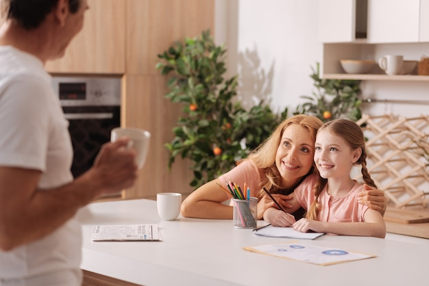 Харизматичный позитивный любящий отец наслаждается чашкой кофе дома и отдыхает, пока жена и маленькая дочь наслаждаются рисованием