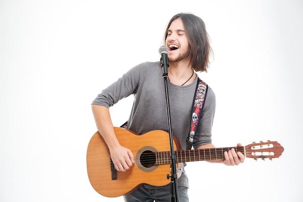カリスマ的な前向きな若者がマイクで歌い、白い背景の上でギターを弾く