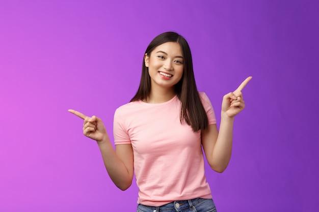 カリスマ的なリラックスしたかわいいアジアの女性の短いヘアカットは横向きで、さまざまな選択肢を紹介し、左右の製品を示し、楽しく笑顔で、簡単に決定を下し、紫色の背景を立てます。