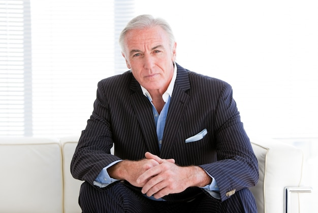Charismatic senior businessman sitting on a sofa