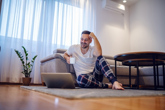 Charismatic smiling caucasian man in pajamas sitting on the floor in living room holding mug with coffee and looking at laptop.