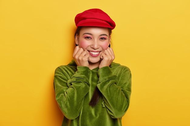 동양적인 외모를 가진 카리스마 넘치는 부드러운 여성, 뺨을 만지고, 최고의 하루를 즐기고, 밝은 빨간 모자와 벨벳 녹색 스웨트 셔츠를 입습니다.