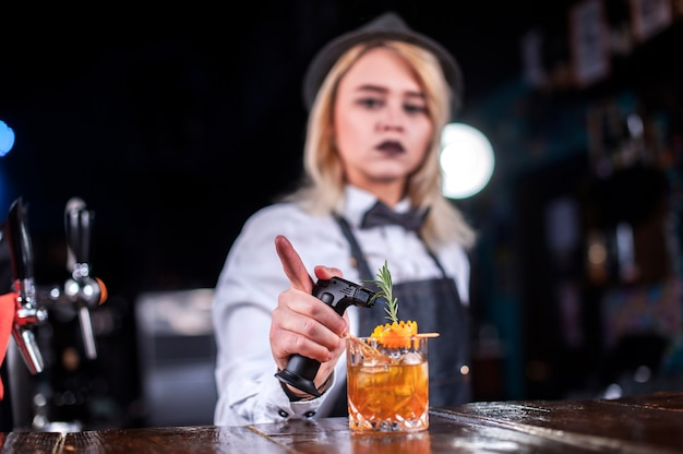 Charismatic woman bartender intensely finishes his creation while standing near the bar counter in bar