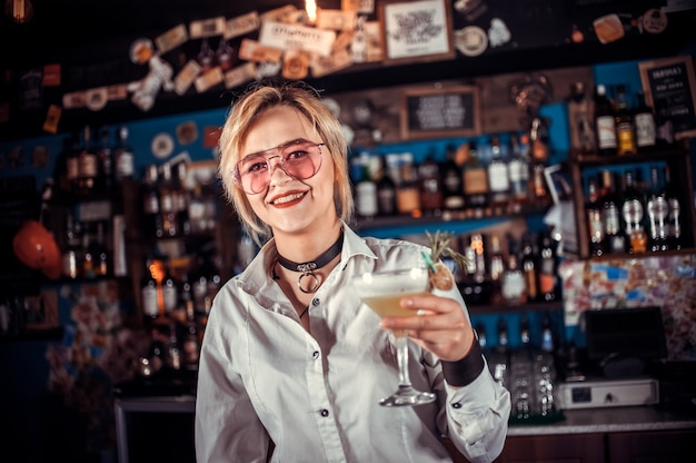 Charismatic woman bartender places the finishing touches on a drink at bar