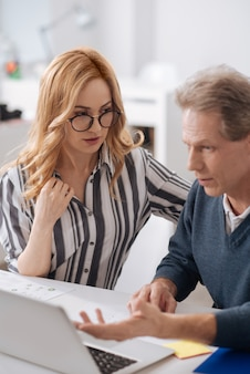 Charismatic young initiative businesswoman sitting in the office next to the coworker while using laptop and seducing the man