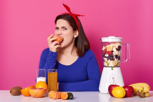 Charismatic young woman, wears bright red headband and blue sweater, bites and eats grapefruit, tastes not good, fruit smoothie in blender, much healthy food in front of eating lady. healthy diet.
