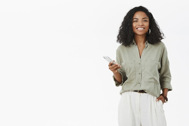Charistmatic affascinante donna afro-americana con acconciatura riccia tenendo la mano in tasca utilizzando smartphone