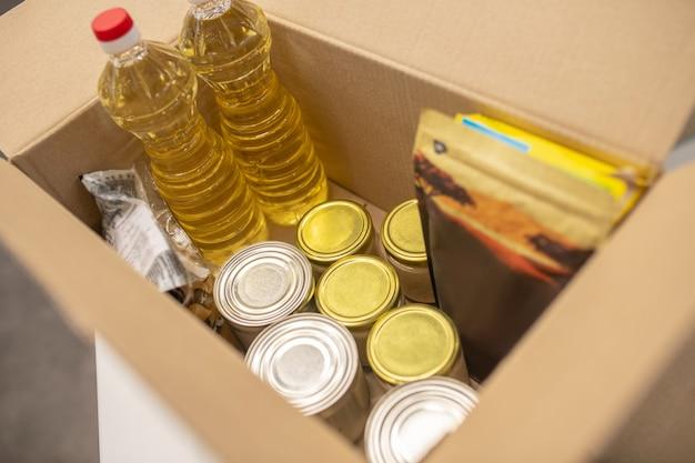 慈善ボックス。チャリティーセンターのオープンダンボール募金箱にきちんとパッケージされた食料品と衣類