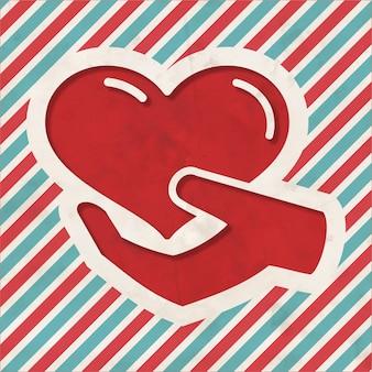 자선 개념-빨간색과 파란색 줄무늬 배경에 손에 심장의 아이콘. 평면 디자인의 빈티지 개념입니다.