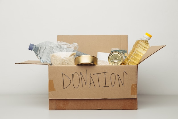 자선 개념. 흰 벽에 다양한 음식과 함께 오픈 기부 골판지 상자