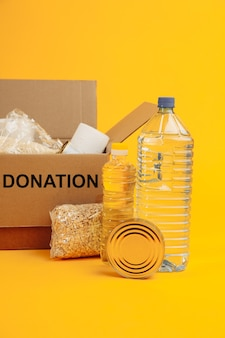 자선 개념. 노란색 벽에 다양한 음식을 기부 골판지 상자를 엽니 다. 수직 이미지