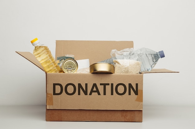 Charity concept. open donation cardboard box with various food.