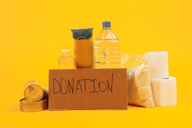 チャリティーコンセプト。貧しい人々のための支援的な住宅や食糧の寄付。黄色の背景に募金箱。