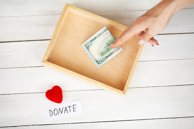 Charity fundraiser box with dollars on white wooden background