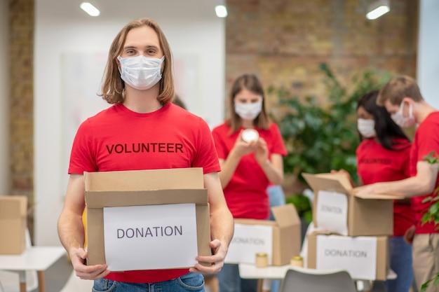자선 단체. 뒤에 기부 상자와 동료와 비문 자원 봉사와 tshirt의 보호 마스크에 즐거운 젊은 남자