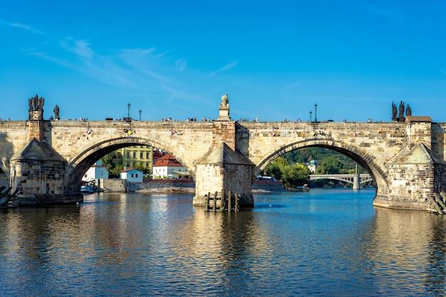 Charles bridge over vltava river against blue sky. prague, czech republic
