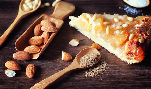 사과와 견과류를 곁들인 샬롯. 견과류와 꿀로 사과 굽기 준비. 나무 테이블에 꿀을 곁들인 사과와 견과류로 만든 디저트 구운 식품.