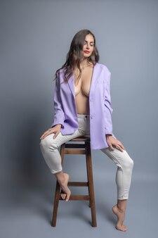 매력. 맨발로 높은 의자에 포즈 속박 재킷에 긴 물결 모양의 머리를 가진 젊은 진정 부드러운 여자