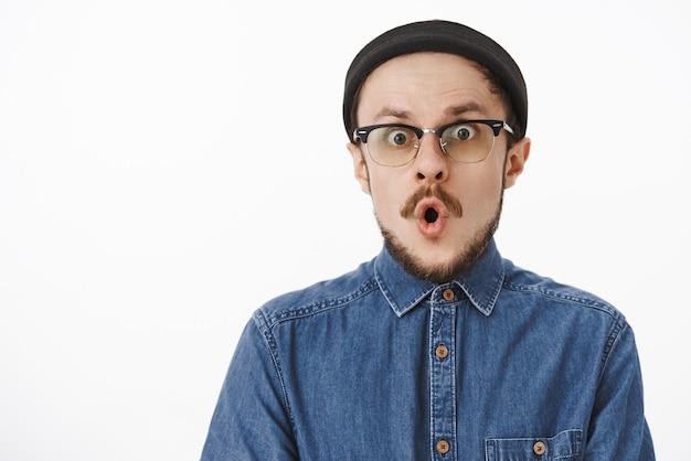Incantato sorpreso, bell'artista creativo maschio in berretto nero e occhiali trasparenti piegare le labbra e trattenere il respiro dallo stupore e dal brivido reagendo a una notizia impressionante