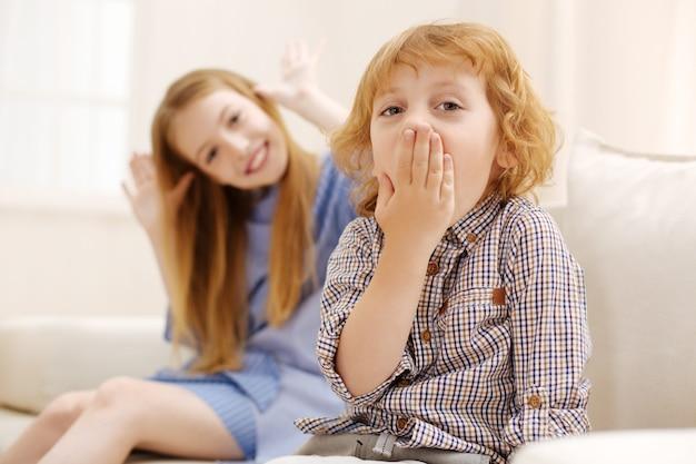 거실에서 소파에 앉아있는 동안 재미와 그의 여동생을 괴롭히는 매력적인 활성 흥분된 아이