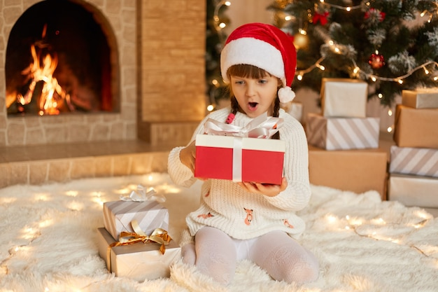 Charming adorable female kid with present box in hand sitting on floor, looking at her gift with surprised facial expression, keeps mouth widely opened, wearing santa hat, pose i festive living room.
