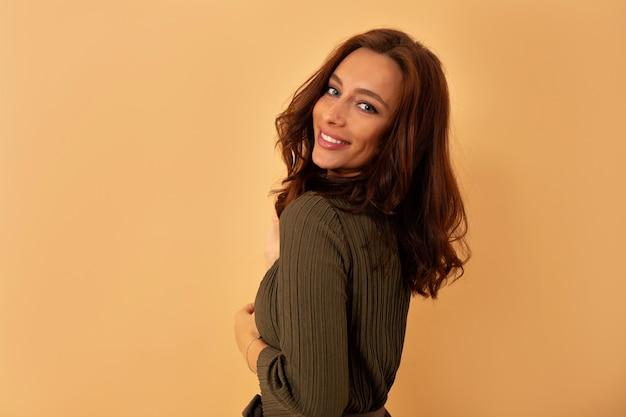 ベージュの壁に向かって写真撮影中に暗いウェーブのかかった髪の魅力的な愛らしい女性が向きを変えます