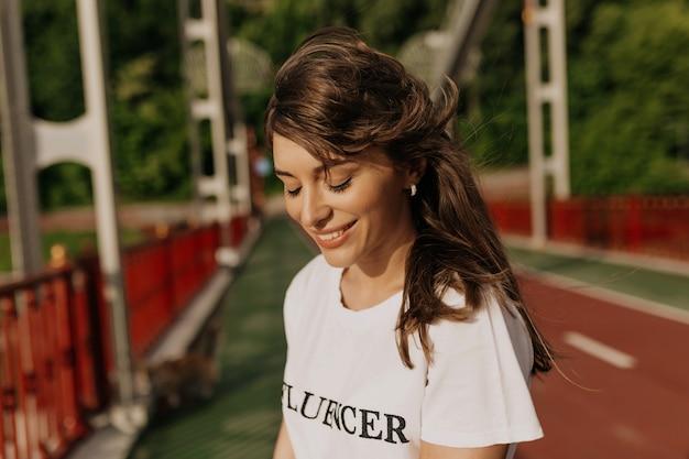 朝日光の下で目を閉じて笑っている白いtシャツを着て長い髪の魅力的な愛らしい女性