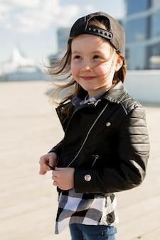 魅力的な愛らしい少女の服を着た革のジャケットとキャップ笑顔と日光の下で海の近くを歩く