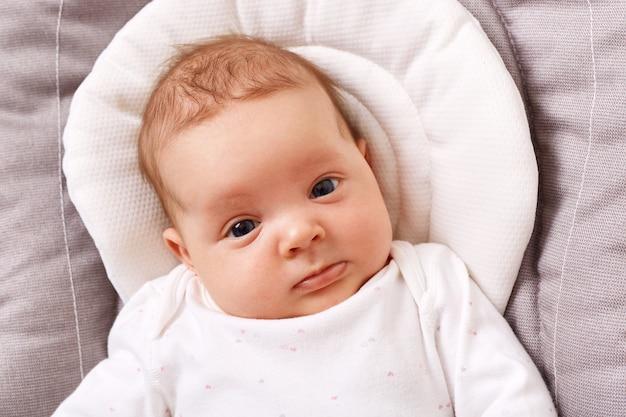 白いシャツを着た魅力的な愛らしい新生児は、正面を見てロッキングチェアに横たわっています