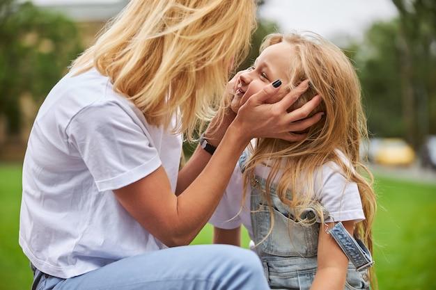 야외에서 휴식하는 동안 손으로 그녀의 딸 얼굴을 즐겁게 잡고 매력적인 성인 아가씨