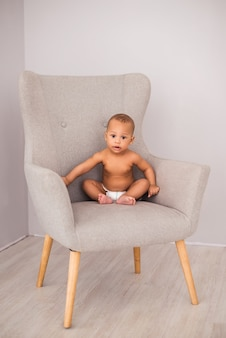 Charming african american baby in a diaper sitting in a chair.