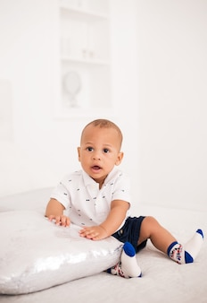 Charming african american baby sitting on the bed