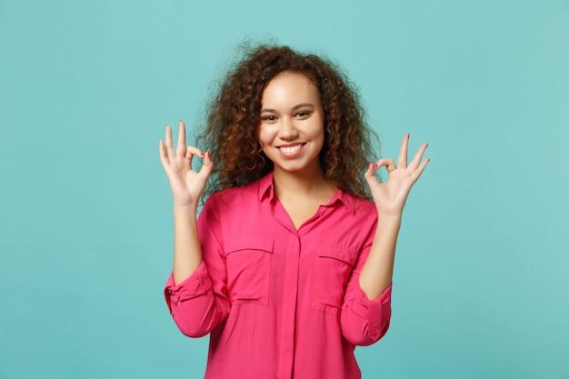 Affascinante ragazza afroamericana in abbigliamento casual che mostra gesto ok che guarda macchina fotografica isolata sul fondo della parete turchese blu in studio. persone sincere emozioni, concetto di stile di vita. mock up copia spazio.