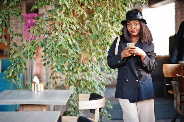 黒のジャケット、帽子、ウエストバッグで魅力的なアフリカ系アメリカ人女性モデルは、携帯電話で自由な時間中にカフェでリラックスできます。
