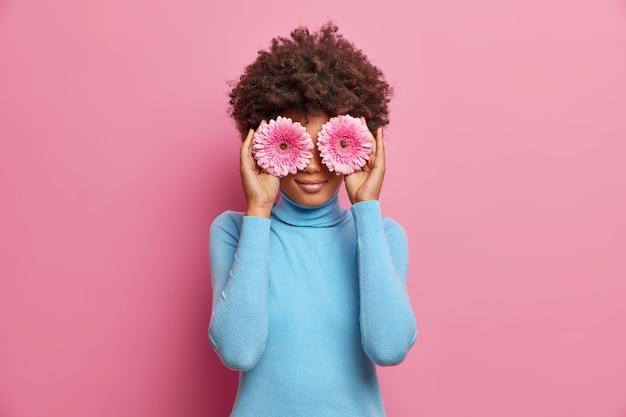 Charming african american woman with natural beauty, holds two gerberas on eyes, dressed in blue turtleneck, poses