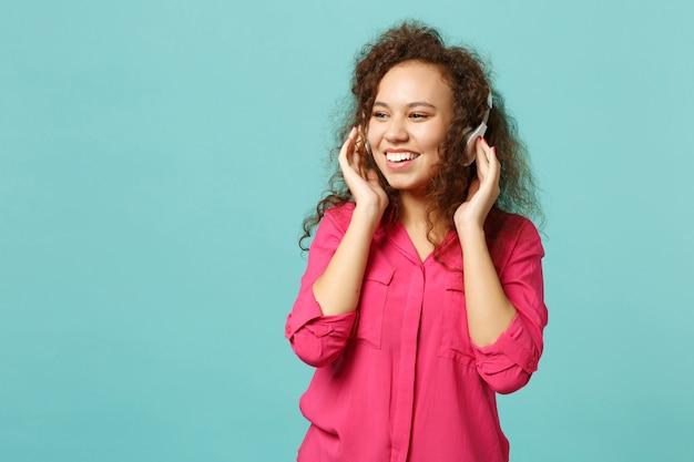 スタジオで青いターコイズブルーの背景に分離されたヘッドフォンで音楽を聴きながら、カジュアルな服を着た魅力的なアフリカの女の子。人々の誠実な感情、ライフスタイルのコンセプト。コピースペースをモックアップします。